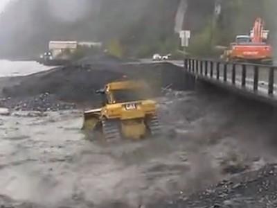 超惊险!推土机司机冒着危险在洪水的冲击下工作